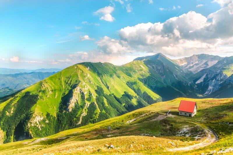 Fristad på Sibillini bergsolnedgång nära sjön arkivbild
