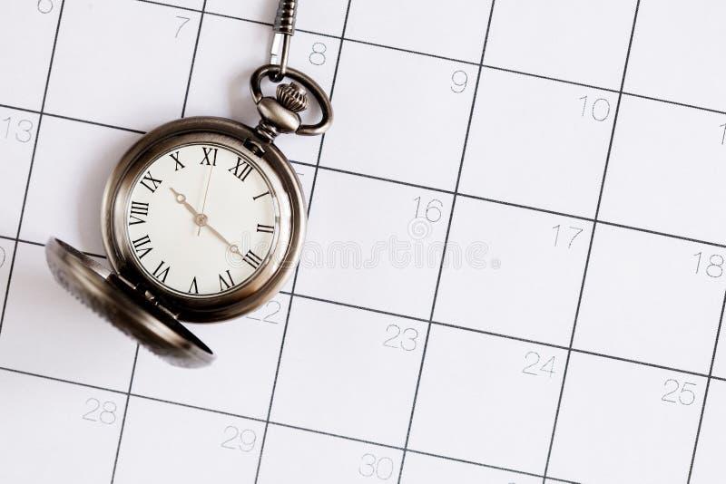 Fristenkonzept-Taschenuhr auf Draufsicht des Kalenderhintergrundes stockfotografie