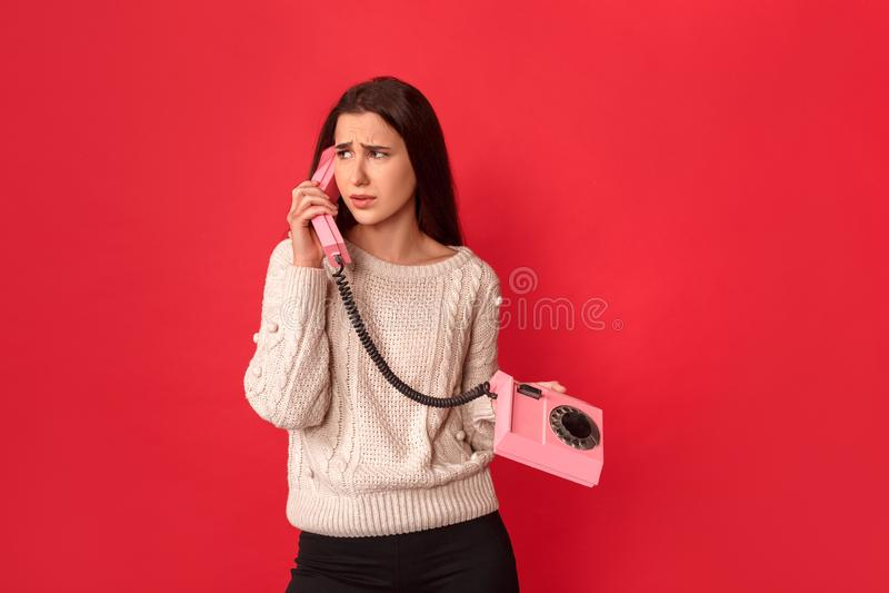 fristil Anseende för ung kvinna på rött samtal på den stationära telefontelefonluren som åt sidan ser olycklig royaltyfri bild