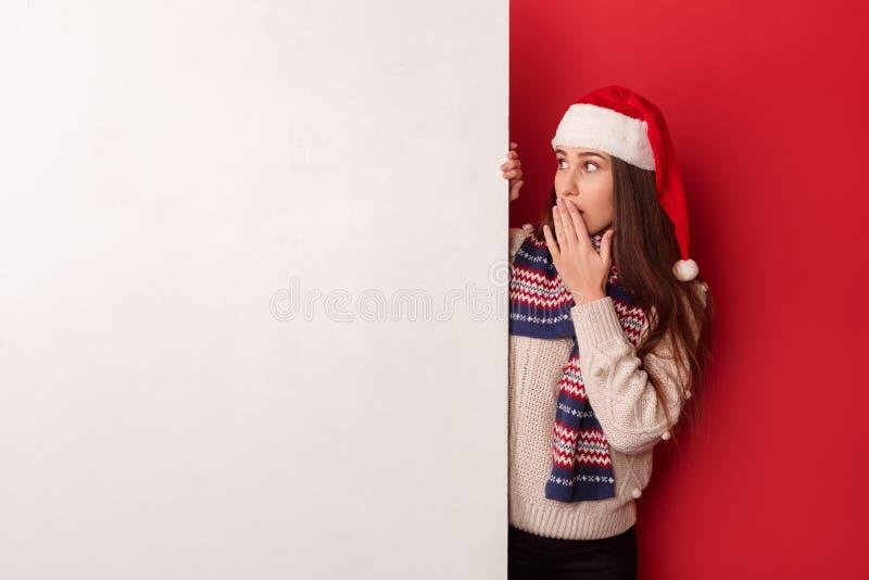 fristil Bärande halsduk- och santa hattanseende för ung kvinna som isoleras på det förvånade röda seende vita brädet fotografering för bildbyråer