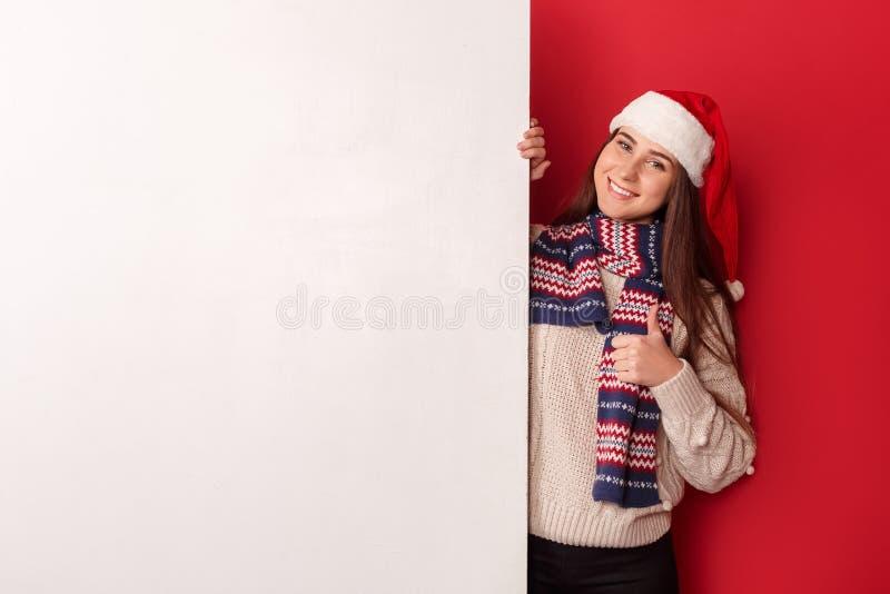 fristil Bärande halsduk- och santa hattanseende för ung kvinna som isoleras på rött med tummen för vitt bräde upp att se kameran arkivfoto