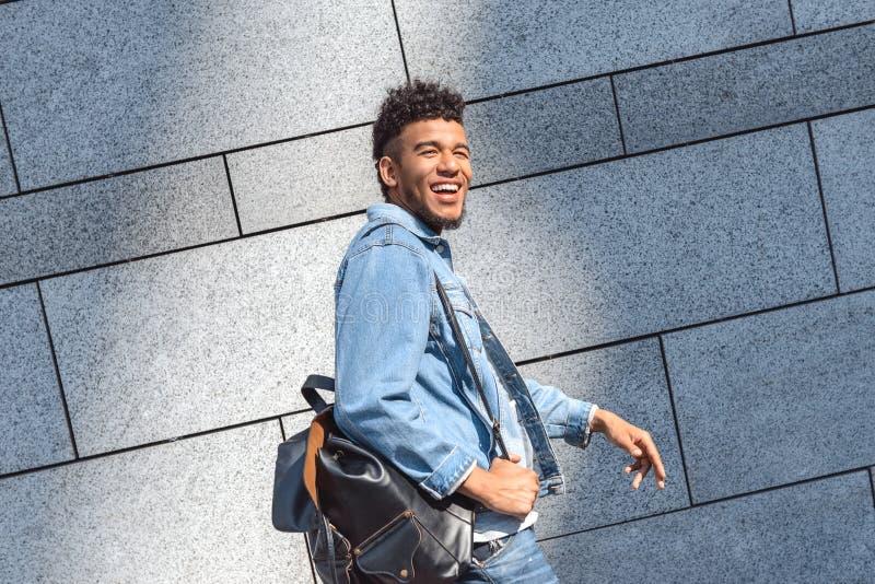 fristil Gå för ryggsäck för mulattgrabb som bärande isoleras på väggen som skrattar gladlynt sidosikt arkivbilder