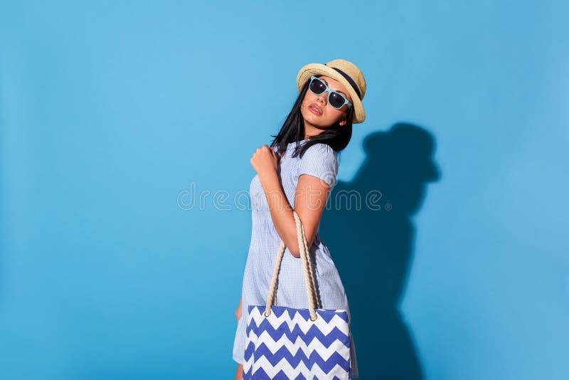 fristil Kvinna i klänningsolglasögon och hattanseende som isoleras på den blåa väggen med påsen som poserar den kalla kameran royaltyfria foton