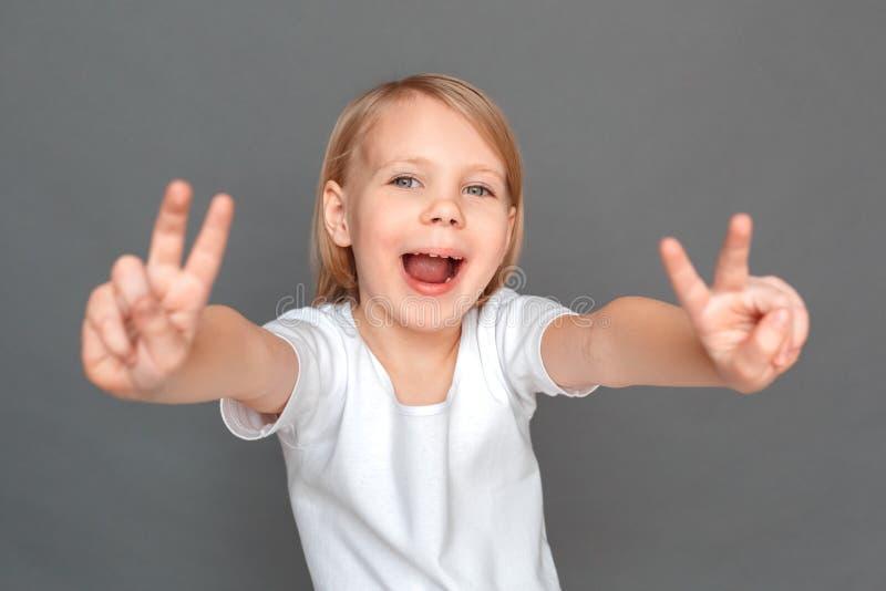 fristil Lilla flickan på gråa visande horn gör en gest le skämtsam närbild royaltyfria foton