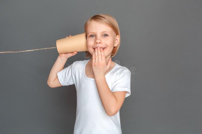 fristil Lilla flickan som isoleras på grå färger med tenn, kan ringa lyssnande le som är upphetsat royaltyfri fotografi