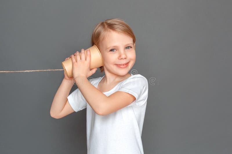 fristil Lilla flickan som isoleras på grå lyssnande konversation på tenn, kan ringa att le som är lyckligt royaltyfri foto