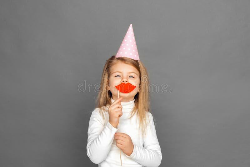 fristil Liten flicka i födelsedaglockanseende på grå färger med partistöttakanter som kysser den glade kameran arkivbild