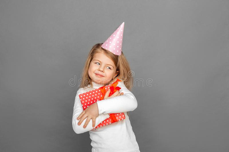 fristil Liten flicka i födelsedaglockanseende som isoleras på grå färger med gåva som ser åt sidan att le som är skämtsamt royaltyfri fotografi