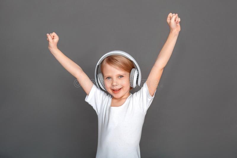 fristil Liten flicka i hörlurar som isoleras på gråa lyssnande sånghänder upp att le som är gladlynt arkivfoto
