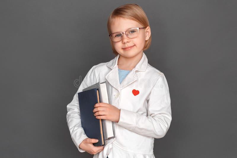 fristil Liten flicka i labblaget och exponeringsglas som isoleras på grå färger med böcker som ler vänskapsmatch royaltyfri fotografi