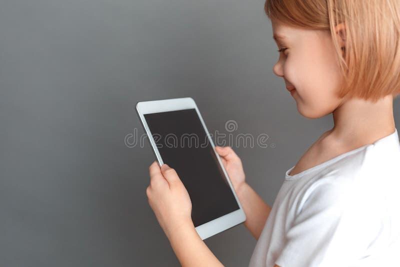 fristil Liten flicka som isoleras på den gråa hållande ögonen på videoen på den digitala minnestavlan som ler gladlynt närbild fö royaltyfri foto