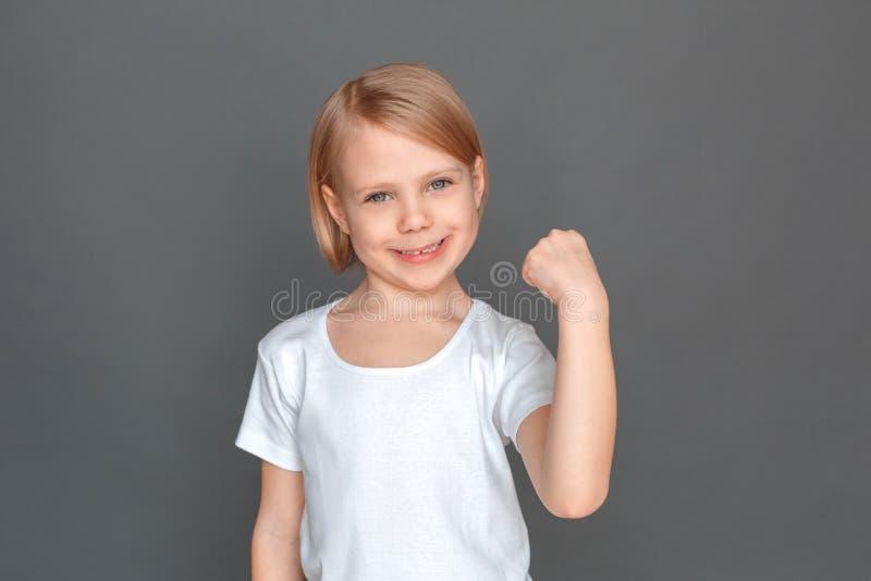 fristil Liten flicka som isoleras på den gråa handen i näven som ler lyckad närbild fotografering för bildbyråer