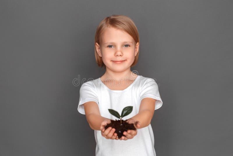 fristil Liten flicka som isoleras på grå färger med växten på jordnärbilden som ler realiteten arkivfoton