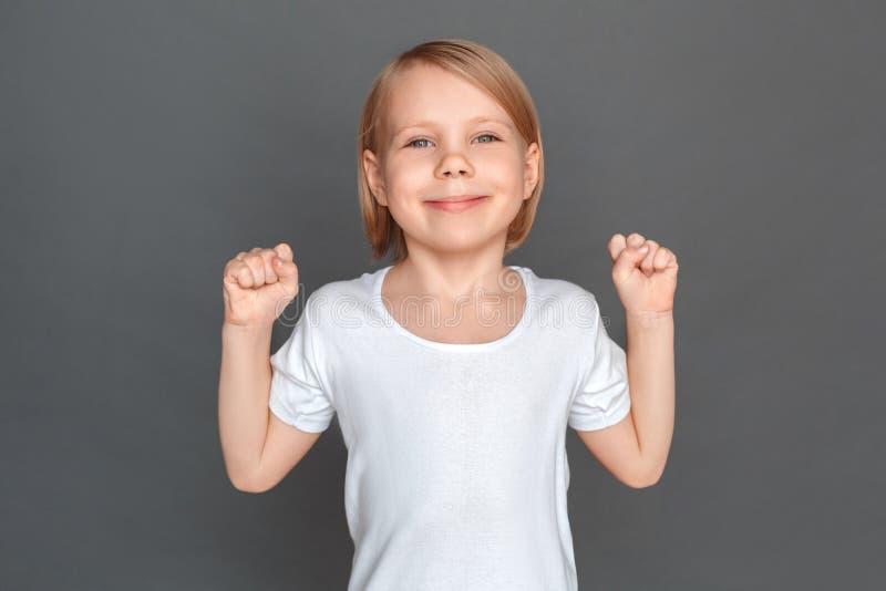fristil Liten flicka som isoleras på gråa händer i nävar som ler åt sidan lyckad närbild royaltyfria foton