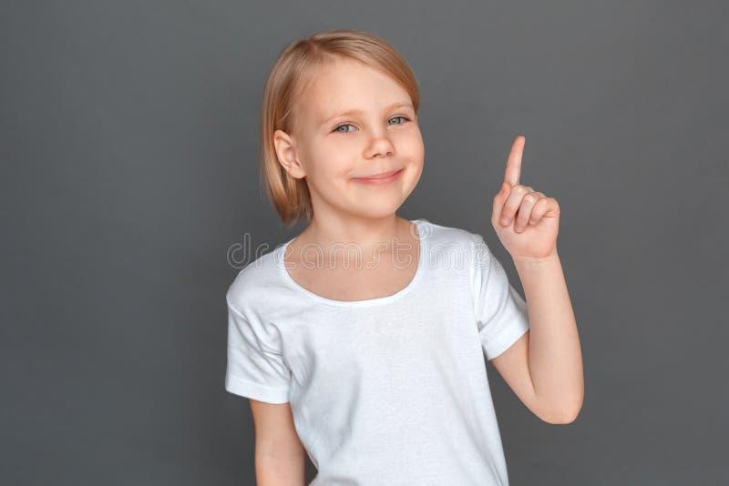 fristil Liten flicka som isoleras på grått peka på utrymme som ler åt sidan glad närbild arkivbild