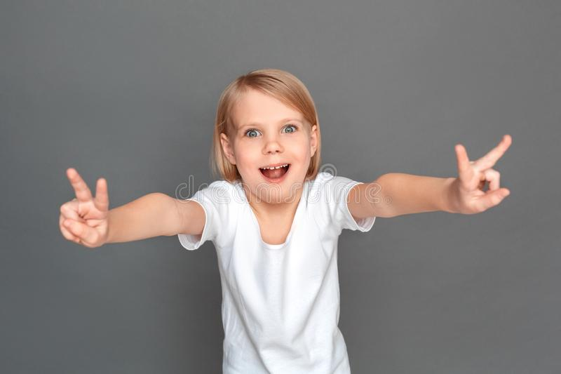 fristil Liten flicka som isoleras på grått visande kallt le för gest som är upphetsat arkivfoto