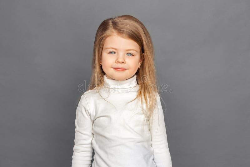 fristil Liten flickaanseende på grått le som är lyckligt till kameran fotografering för bildbyråer