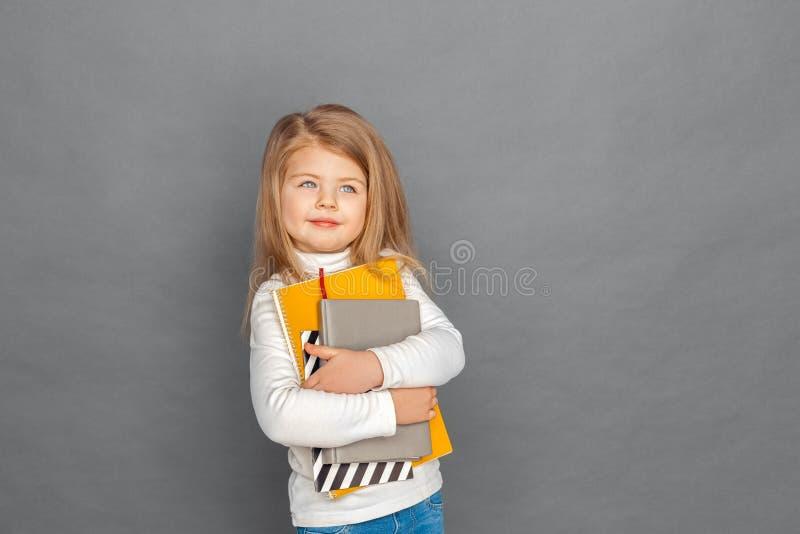 fristil Liten flickaanseende som isoleras på grå färger med anteckningsböcker som ser åt sidan att le som är dreamful arkivfoto