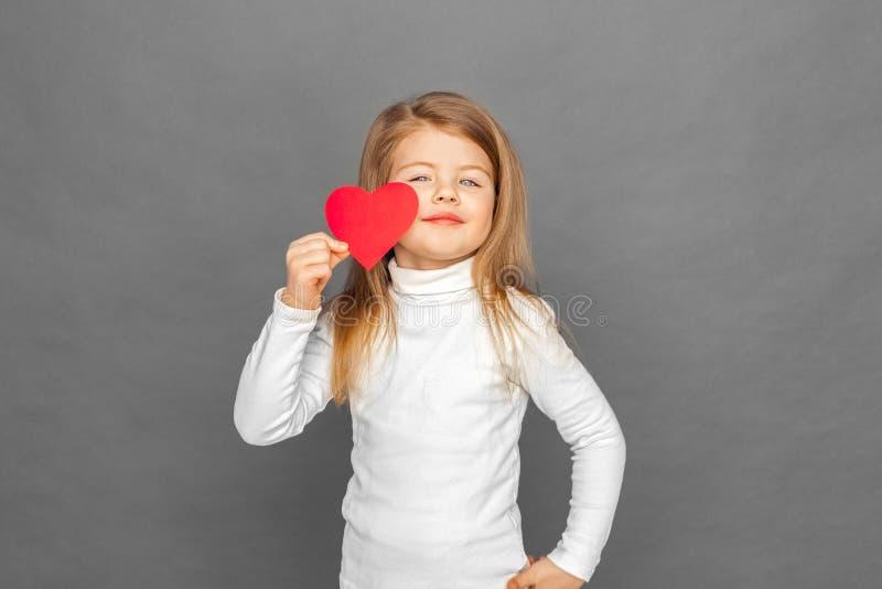 fristil Liten flickaanseende som isoleras på grå färger med att le för hjärtaformkort som är säkert arkivfoto