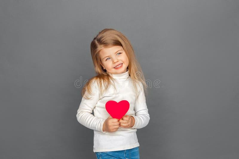 fristil Liten flickaanseende som isoleras på grå färger med hjärtaformkortet som åt sidan ser gladlynt royaltyfri fotografi