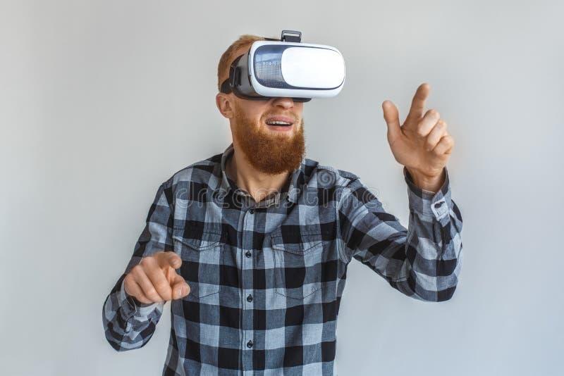fristil Mogen man i virtuell verklighethörlurar med mikrofonanseende som isoleras på grått peka på utrymmenärbilden royaltyfria foton