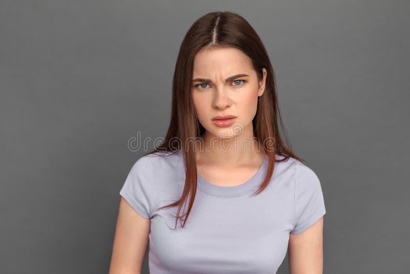 fristil Ung flickaanseende på grå seende bekymrad närbild för kamera royaltyfri fotografi