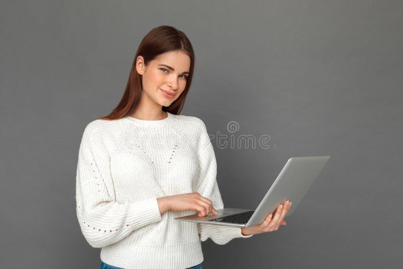 fristil Ung flickaanseende som isoleras på den gråa bläddra bärbara datorn som ser den glade kameran royaltyfri fotografi