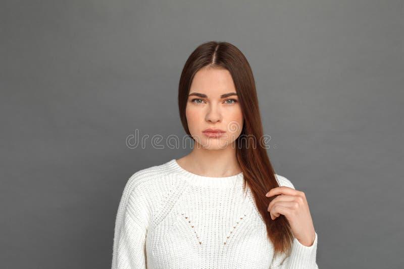 fristil Ung flickaanseende som isoleras på fundersam närbild för grått rörande hår royaltyfria foton