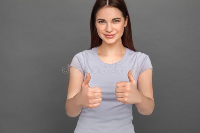 fristil Ung flickaanseende som isoleras på gråa visande tummar upp att le lycklig närbild fotografering för bildbyråer
