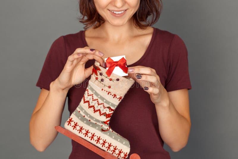 fristil Ung kvinna på den gråa sättande gåvan in i dekorerad socka som ler gladlynt närbild fotografering för bildbyråer