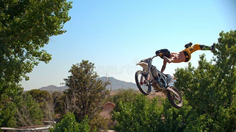Fristilmotocrosscyklisten utf?r tricket i hopp p? fmxkonkurrenser fotografering för bildbyråer