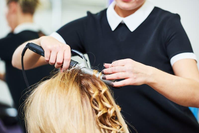 Frisur im Schönheitssalon Friseur, der Frisur mit Locke zum wonam macht lizenzfreies stockbild