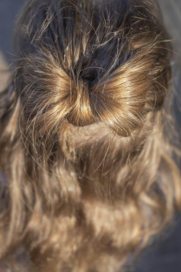 Frisyr med en pilbåge i en blond flicka royaltyfria bilder