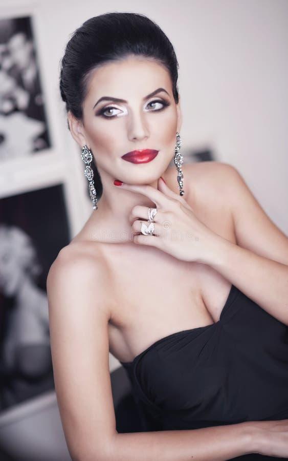 Frisyr och smink - härlig kvinnlig konststående med härliga ögon elegans Äkta naturlig brunett med den svarta klänningen fotografering för bildbyråer