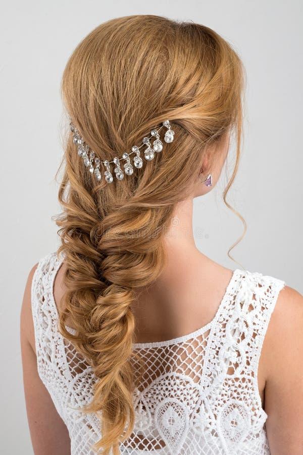 frisyr Samlat i ett blont hår för flätad tråd med en härlig garnering royaltyfri bild