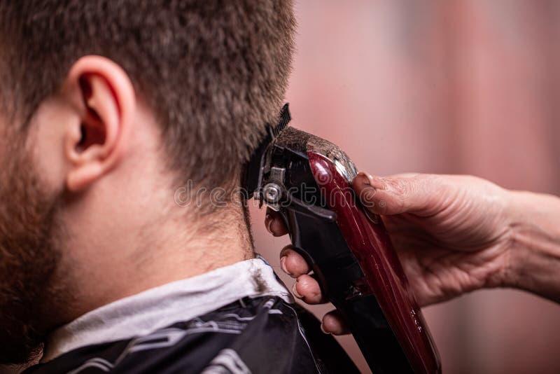 Frisyrcloseup Händer som rymmer en hårclipper Barberare stilskapelse, skönhet Sk?nhetsalong arkivfoto