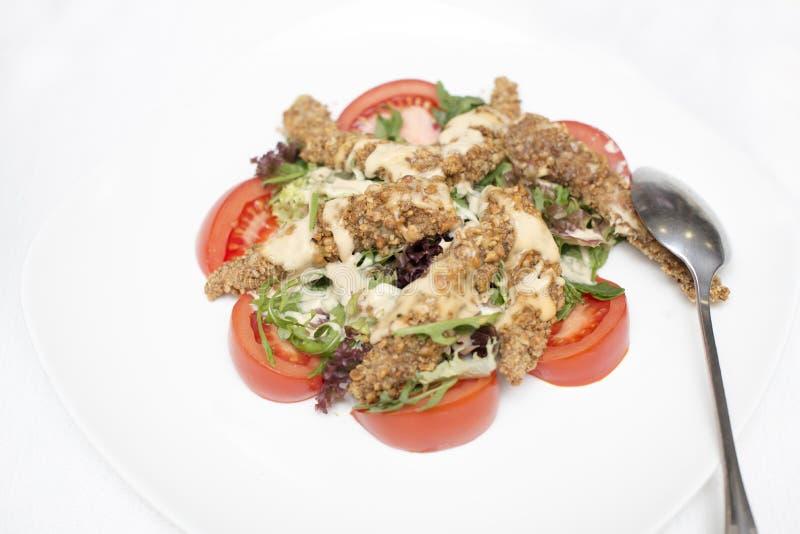Frit dans un plan rapproché de salade de poulet pané et de légume frais d'un plat sur une table blanche Vue de ci-avant photos stock