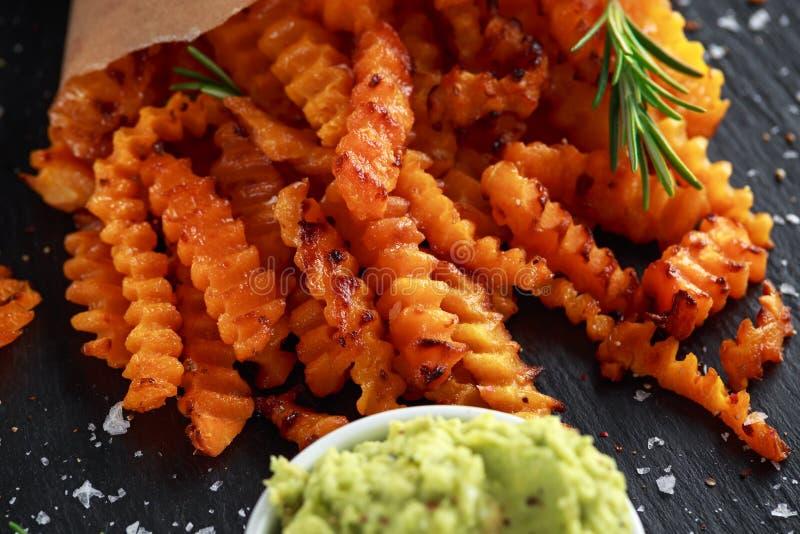 Fritadas cozidas da polpa de butternut com sal do mar, alecrim no cone do papel Microplaquetas da abóbora e mergulho do quacamole fotos de stock
