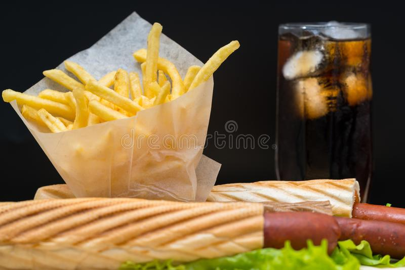 Fritadas na película de plástico ao lado dos cachorros quentes e da soda imagem de stock royalty free