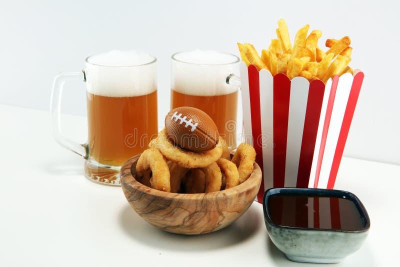 Fritadas y anillos de cebolla para el fútbol en una tabla Grande para el juego del cuenco fotos de archivo libres de regalías