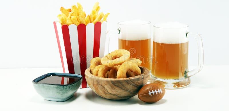 Fritadas y anillos de cebolla para el fútbol en una tabla Grande para el juego del cuenco imagenes de archivo