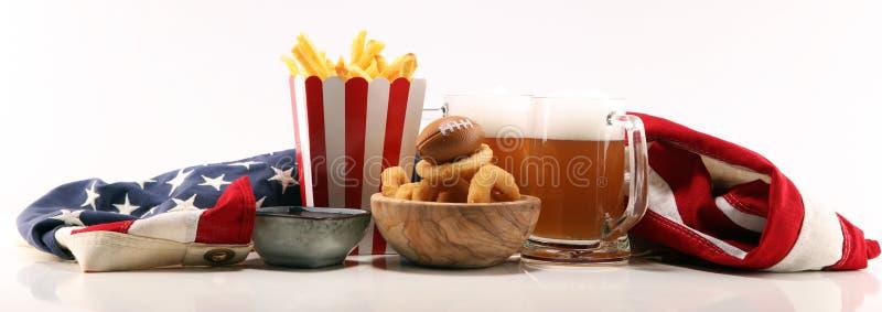 Fritadas y anillos de cebolla para el fútbol en una tabla Grande para el juego del cuenco imagen de archivo libre de regalías