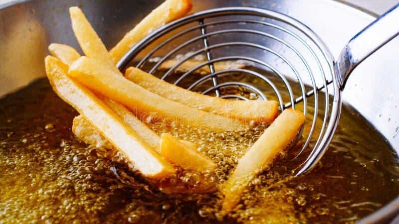 Fritando batatas fritas na frigideira fotografia de stock