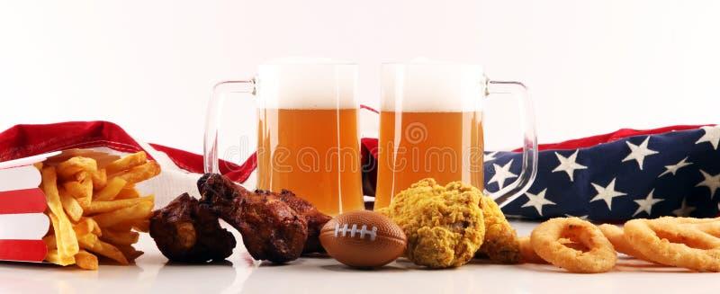 Frites, casse-croûte salés, football et bière sur une table Grand pour des projets de jeu de cuvette photos stock