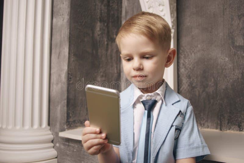 Fritid, barn, teknologi, internetkommunikation och folkbegrepp - le pojken med det smsande meddelandet för smartphone royaltyfri foto