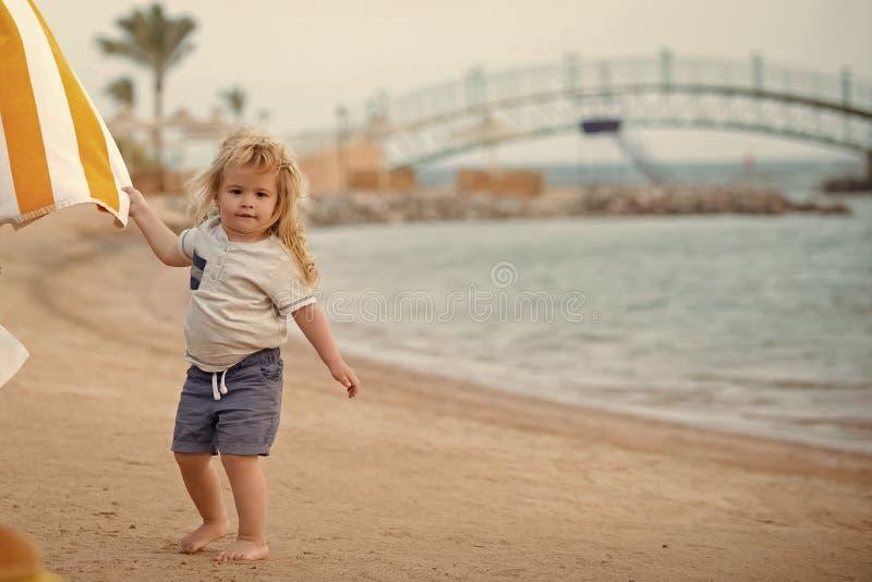 Fritid för barn` s Handduk för vit och för guling för litet barn för pojke innehav gjord randig royaltyfri foto