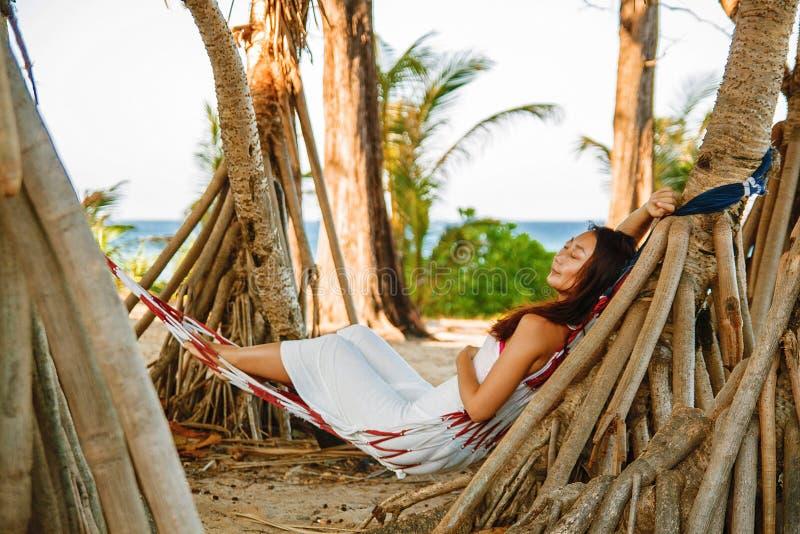 Fritid för leendet för den härliga unga asiatiska kvinnan för ståenden svänger lycklig på hängmattan runt om det strandha royaltyfri bild