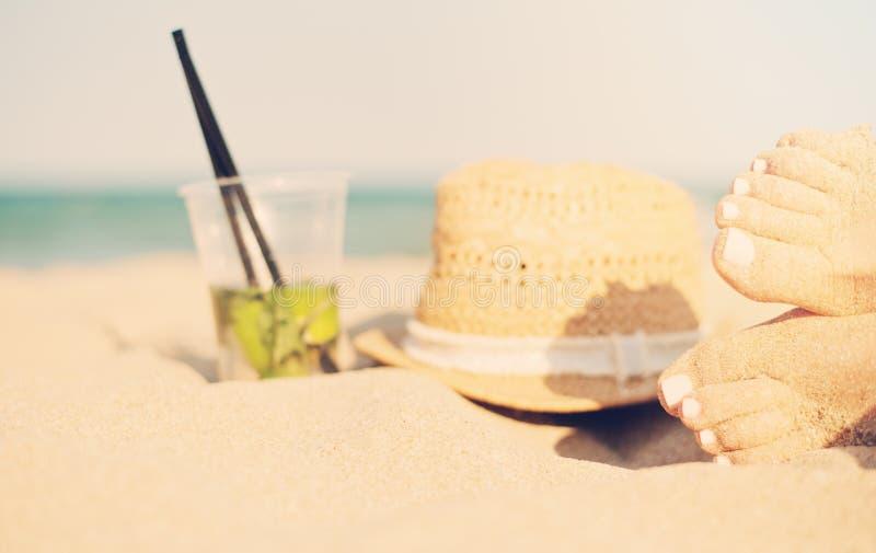 Fritid i sommar - som är härlig av sexig kvinnafot, kvinnlig lägger benen på ryggen på den sandiga stranden med hatten och mojito royaltyfria foton