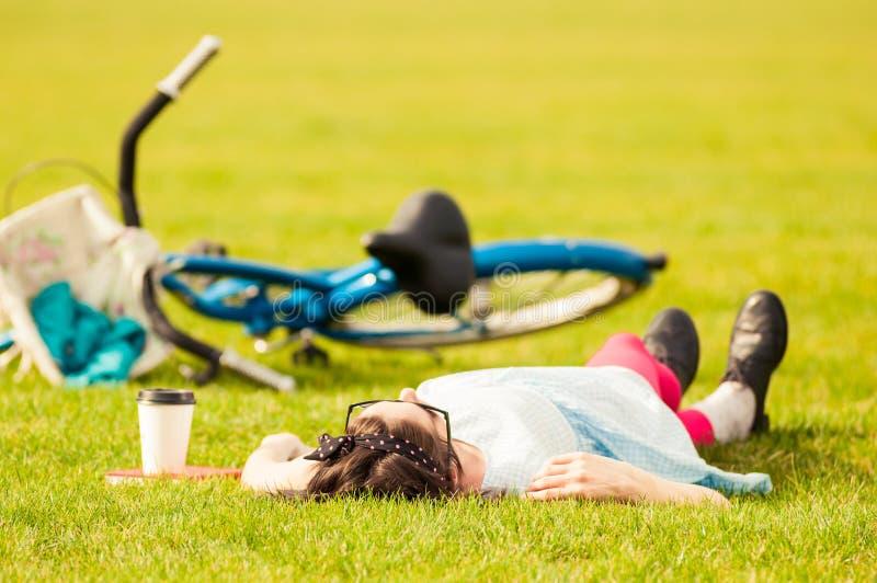 Fritid och avkopplingbegrepp med hipsterkvinnan som ligger på gräs arkivbild