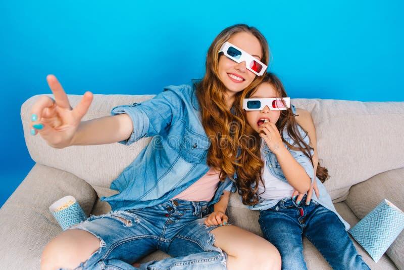 Fritid tillsammans av att förbluffa den härliga modern med hennes unga dotter på soffan som isoleras på blå bakgrund slitage royaltyfri fotografi